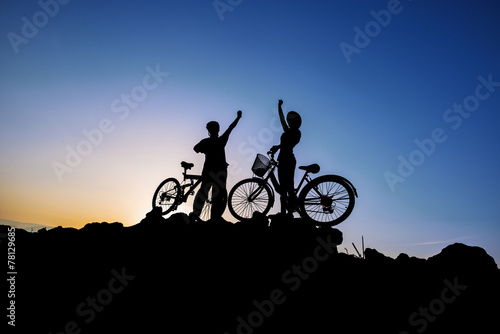 Silhouette of a man and girl on mountain bike at sunset