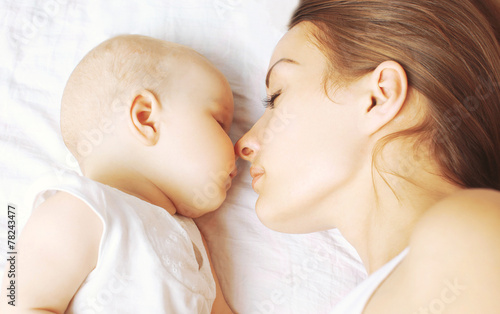 Photo  Baby and mother sleeping together on the bed