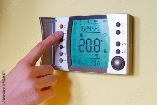 Photo  Closeup of a woman's hand setting the room temperature on a mode