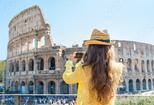 Fotografia, Obraz  Young woman taking photo of colosseum in rome, italy. rear view