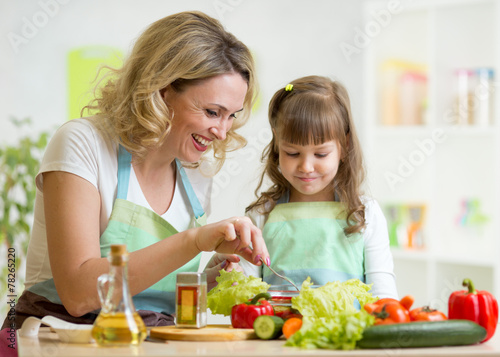 Papiers peints Cuisine mother and her child preparing and tasting healthy food