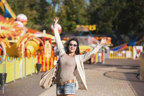 Papiers peints Attraction parc Amusement park rides. A young woman is happy and jumps.