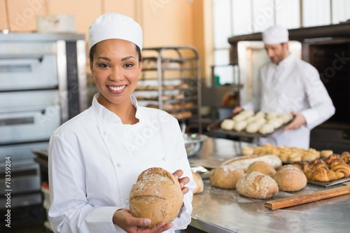 Tableau sur Toile Pretty baker smiling at camera with loaf