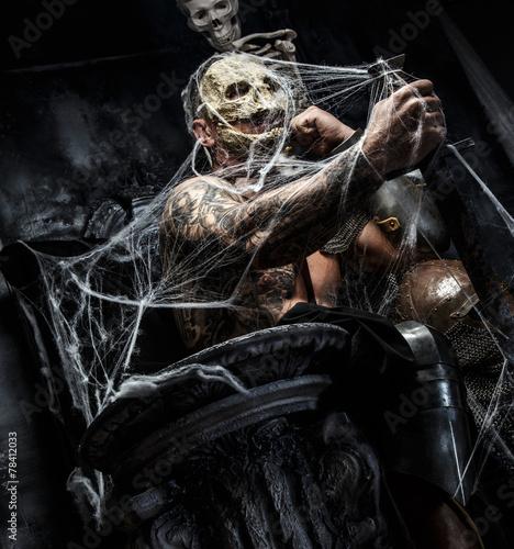 Fényképezés  Muscular man with skull on his face.