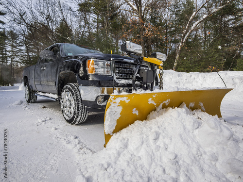 Pickup truck plowing snow