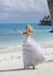 beautiful woman in dress of bride at edge of sea