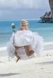 beautiful woman in dress of bride jumps at sea edge.