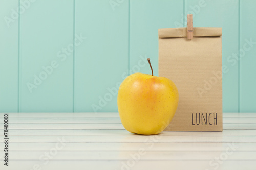 Fotografía  An apple and a paper bag with lunch. Vintage Style.