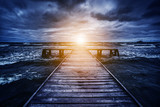 Old wooden jetty during storm on the ocean. Abstract light