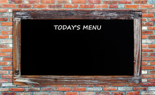 Today's Menu On Vintage Chalk Board Over Brick Wall Background