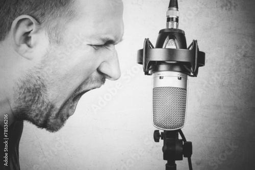 Fotografia Rock vocalist screaming to the studio microphone