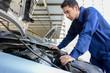 Auto mechanic (or technician) checking car engine