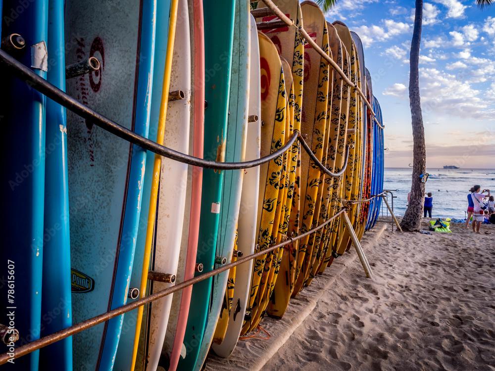 Fototapeta Colourful surfboards stacked up on Waikiki Beach at sunset.