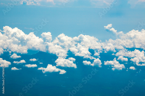 Ocean coastline, land, mountains and clouds airplane view