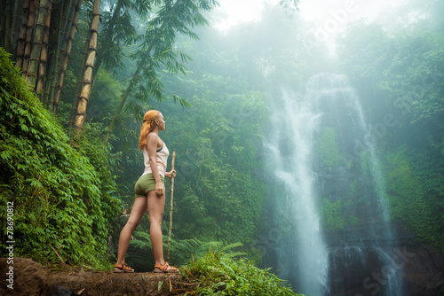 In de dag Bali Female adventurer looking at waterfall
