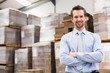 Smiling manager with arms crossed in warehouse