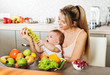 Happy young mother with a baby in the kitchen interior. Fresh ve