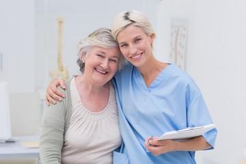 Friendly nurse with arm around senior patient in clinic