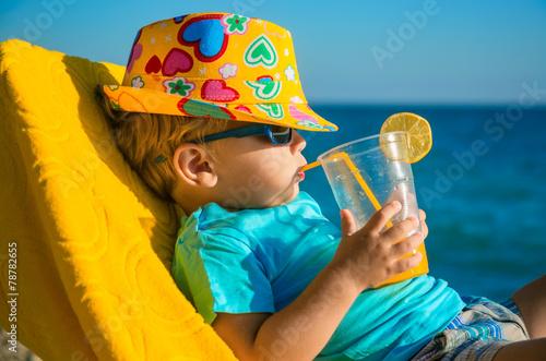 Fotografia, Obraz Boy kid in armchair with juice glass on beach