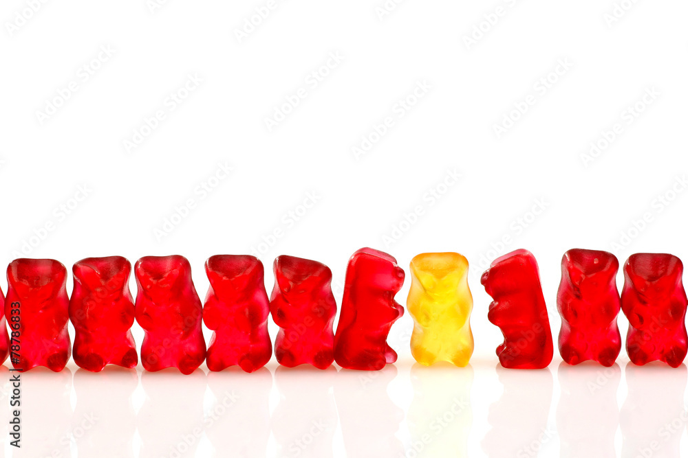 Fototapeta row of red gummy bears and a yellow one isolated on white