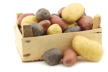 Yellow, Red And Purple Potatoes In A Wooden Crate On A White Bac