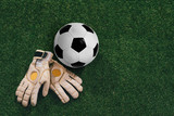 Fototapeta Sport - Soccer ball and goalkeeper gloves