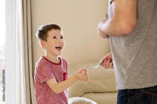 Boy receiving pocket money (allowance) from father Canvas Print