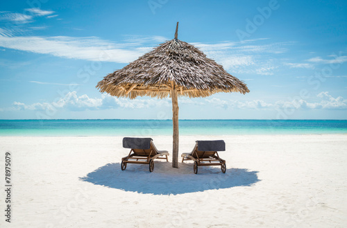 2 wooden sun loungers under a thatched umbrella on a Zanzibar tr