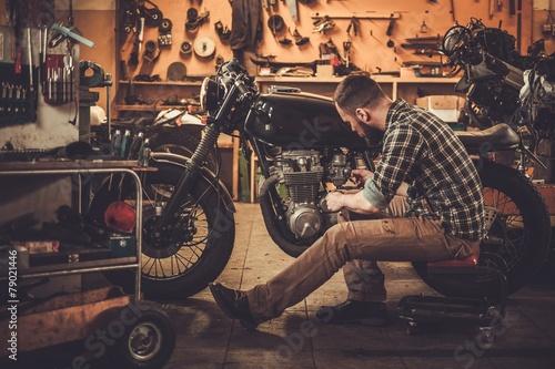 Fotografia Mechanic building vintage style cafe-racer motorcycle