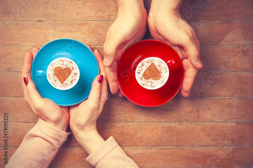 Women and man holding cups of coffee