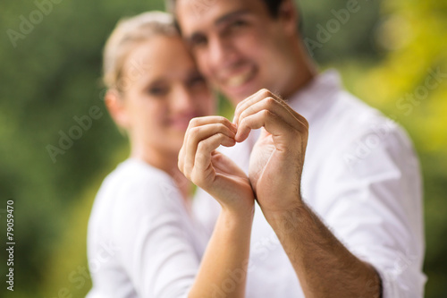 Photo  young couple making heart with hands