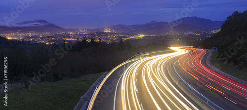 Poster Autoroute nuit car lights at night on the road going to the city
