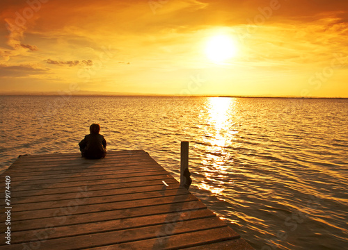 Fotobehang Pier niño pensando frente al sol