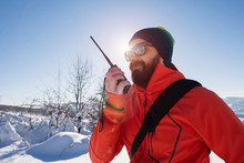 Rescue Man Talking With Portable Radio On Mountain Snow Landscap