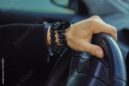 Photo Color image of adult male hand with watch and bracelet in car