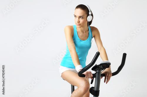 Fototapeta premium Ćwiczenia na rowerze stacjonarnym, kobieta w fitness klubie