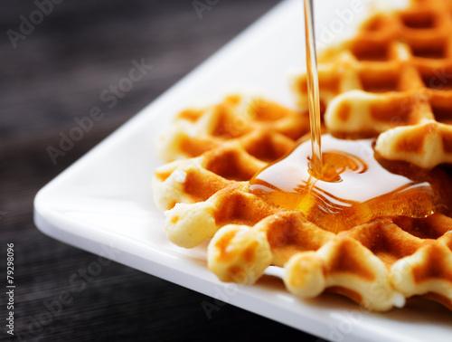 Fotografía  Honey pouring on a fresh waffles
