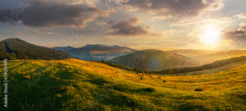 Fotobehang Platteland agricultural field in mountains at sunset