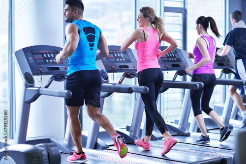 Group of people running on treadmills Fototapeta