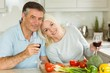 Happy mature couple having red wine while making dinner