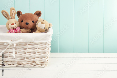 In de dag Retro Stuffed animal toys in a basket on the floor. Turquoise wainscot