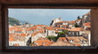 DUBROVNIK, CROATIA - MAY 26, 2014: View on Old city rooftops through stone window in city walls.