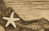 Starfish and fishnet on weathered  wood in sepia