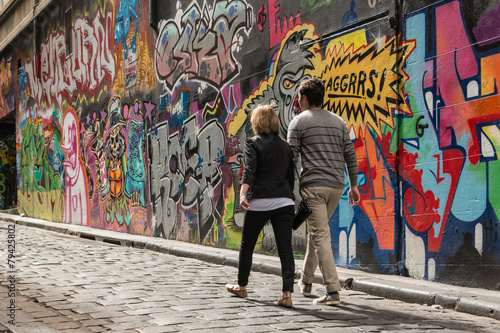 Foto auf AluDibond Graffiti young couple walking past graffiti wall in Melbourne