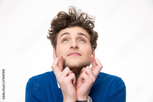 Fényképezés  Young handsome man with crossed fingers over white background