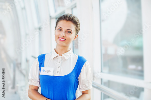 Beautiful young flight attendant in the airport. Wallpaper Mural
