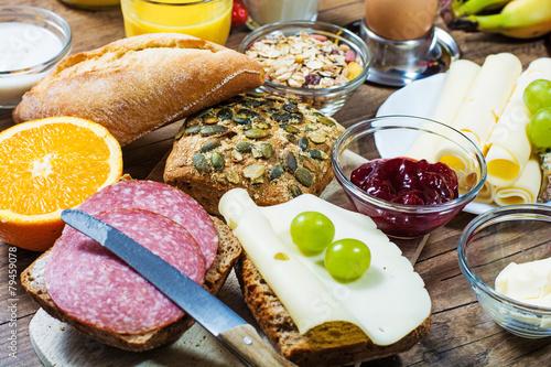 Fototapeta gedeckter Frühstückstisch mit Brötchen, Käse, Obst und Marmelade obraz