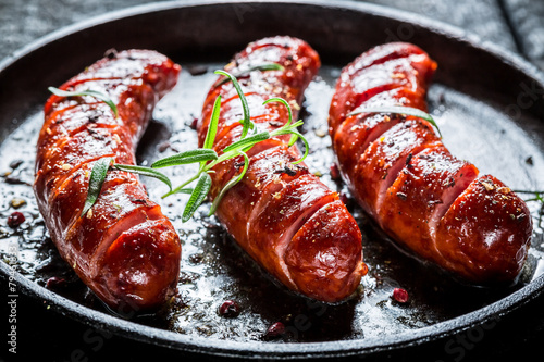 Obraz na plátně Grilled sausage with fresh rosemary on hot barbecue dish