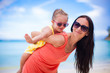 Adorable little girl and happy mom during tropical beach