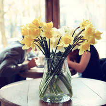 Table In The Cafe With Lent Lily And Loving Couple At Background